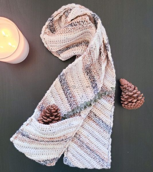 Crochet Pocket Scarf laid flat with pinecones.