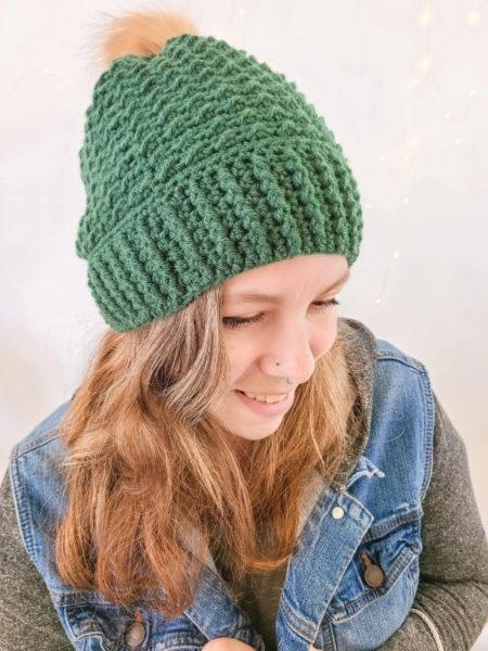 Designer wearing the Arctic Crochet Beanie in green.