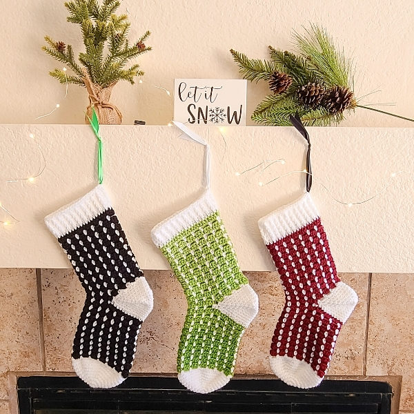 3 Crochet Christmas Stockings made from pattern hanging in front of fire place.