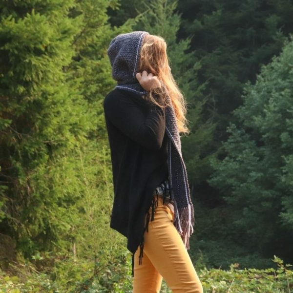 Adult wearing crochet hooded scarf, forest background.