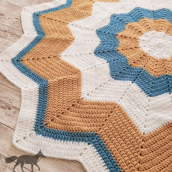 This image shows the crochet star baby blanket laying flat, at an angle, to show all of the peaks and valleys created while crocheting.