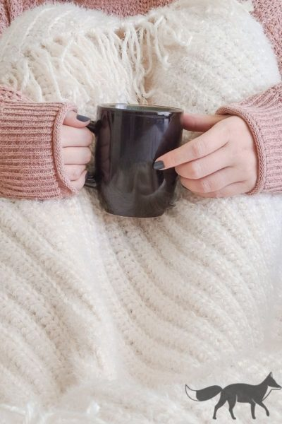 bulky crochet blanket shown being used over the knees, with person holding a cup of coffee