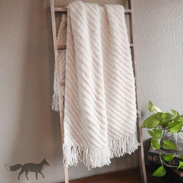 easy half double crochet blanket, shown hanging on blanket ladder.