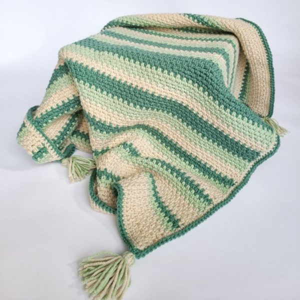 Moss stitch baby afghan shown laid over crate, as to show drape and functionality
