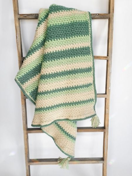 Finished crochet baby afghan pattern, shown hanging on ladder with some drape.