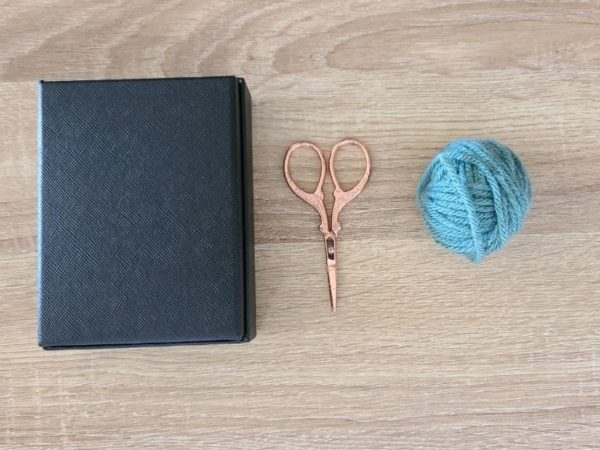Yarn, scissors and a small box.