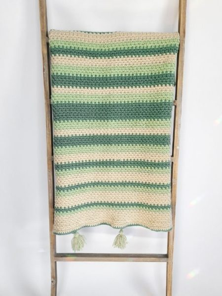 crochet baby afghan, in white, light green and dark green stripes hanging on a blanket ladder with white background.