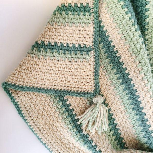 Easy crochet baby afghan showing details of border and tassel in corner.