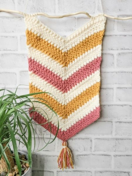 Crochet wall hanging pattern shown finished, hanging in home.