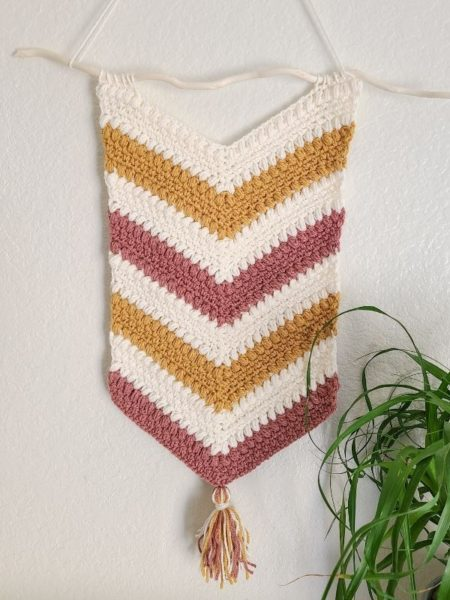 Crochet wall hanging pattern shown finished and hanging in home with plant.