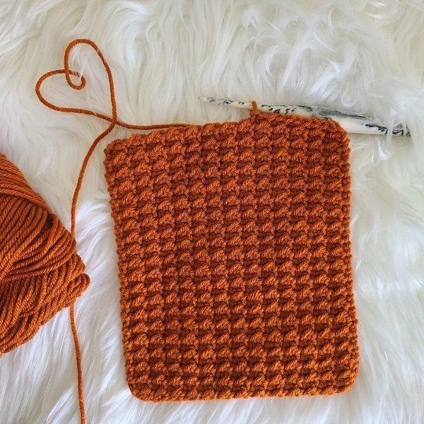 Swatch of crochet stitch in orange.