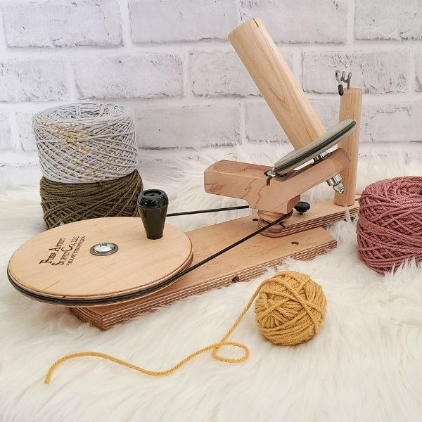 The Best Crochet Tools - wooden bespoke yarn winder shown with yarn cakes.