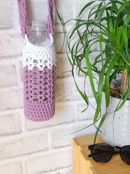 Crochet Water Bottle Holder shown in two colors, white and purple.