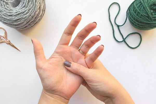 Image shows author holding left hand in their right hand, with thumb in palm as if giving a massage to stop pain while crocheting