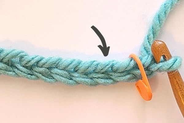 This image is the same as the above for the crochet moss stitch tutorial, however, it now shows a stitch marker placed around the first 2 chains.