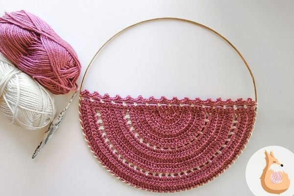 Furls Wander yarn in Dragonfruit and Snow, shown next to crochet wall hanging free pattern.