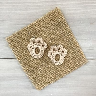 Shows a crochet earring pattern that are cute little paws using Lace yarn weight.