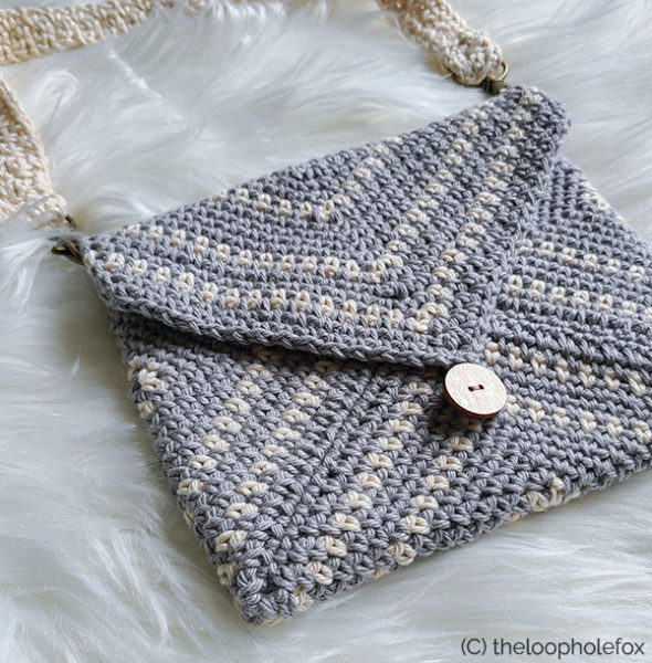 Crochet clutch pattern shown laying flat, close up of detail such as button and stitches.