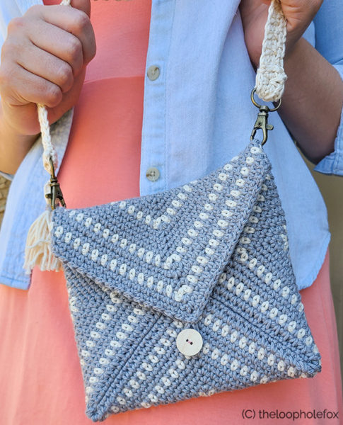 Woman holding the crochet clutch pattern sample, close up of bag.