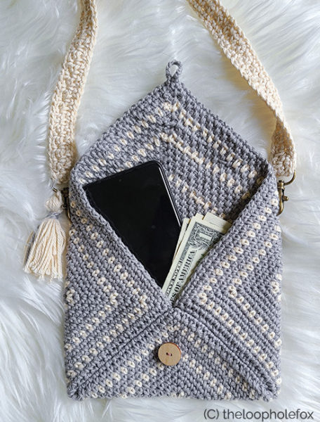 Image shows the crochet clutch pattern sample open with phone and dollar bills inside, to reference size.