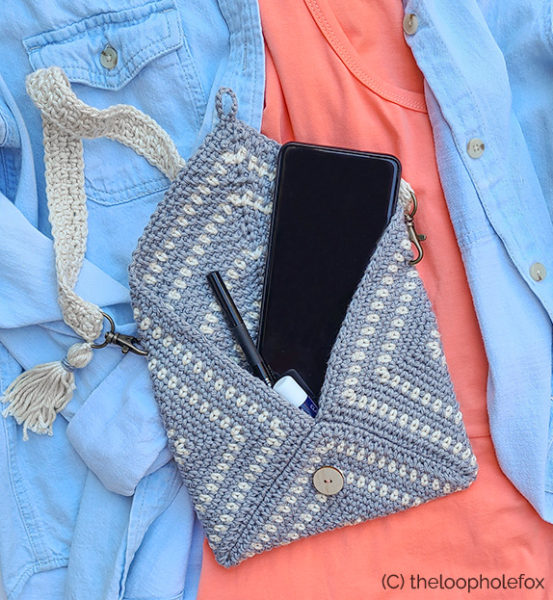 Flat lay of crochet clutch pattern, laying open. Bag is sitting on a jean jacket and peach dress, with phone and Chapstick inside to reference size.
