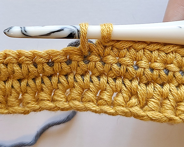 This image shows that when you yarn over and pull through both the slip knot and the stitch, you shouldn't have anything but the yarn you're working with on your hook.