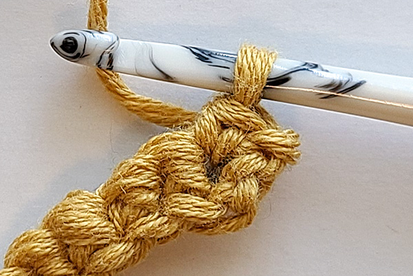"""This image shows the first single crochet of this non stretchy crochet strap complete and references how the """"fishing line"""" can't be seen."""