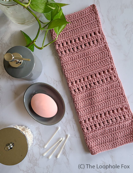 It shows the crochet hand towel laying folded in half on marble, with bathroom items such as a soap dispenser and soap tray as well as a plant.