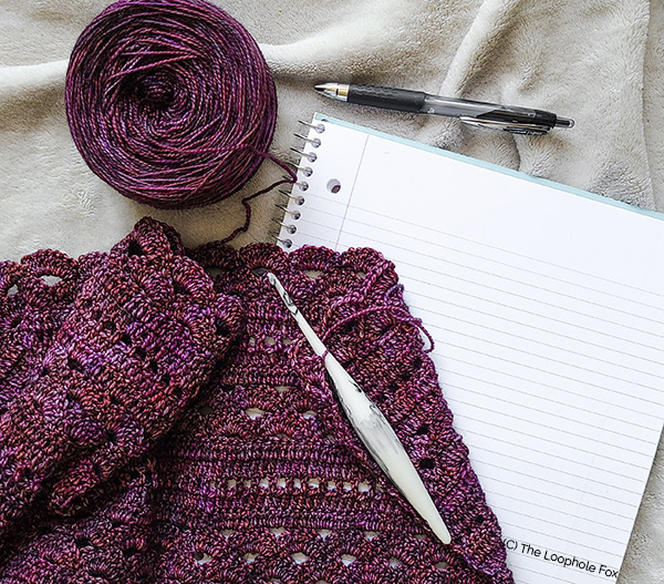 """This image is a """"work in progress"""" picture, showing the shawl laying over a new notebook with the yarn cake, a pen and crochet hook."""