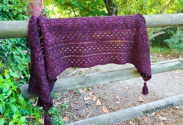 Image shows a crochet rectangle shawl draped on a wooden fence. The shawl is purple and shows the open stitch work and is surrounded by greenery in different shades of green.