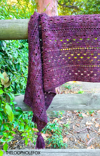 Image is a close up of one side of the crochet rectangle shawl draped on a wooden fence.