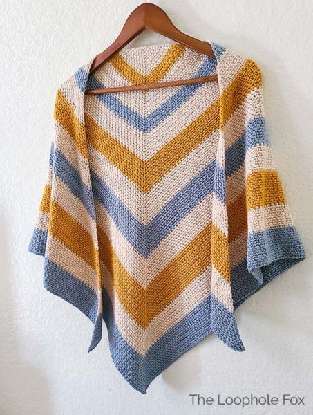 This image shows the moss stitch crochet shawl hanging on a wooden hanger on a white wall.