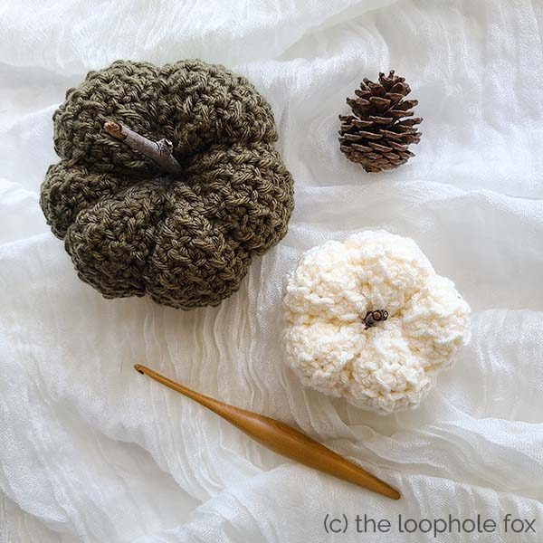 Crochet Pumpkin Pattern shown from top down to view the tops of the pumpkins as well as their shape after creating the ribbing. Two pumpkins sit diagonally on the image. One is larger and a dark green, the other is smaller and white.