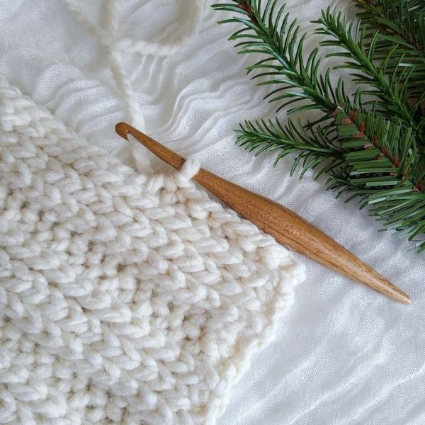 This image shows a work in progress of the crochet ribbed beanie, with a wooden crochet hook still on loop.
