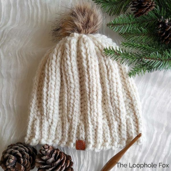 This image shows the ribbed crochet beanie pattern made in super bulky yarn, Lion Brand's Wool Ease Thick and Quick in Fisherman (creamy white).