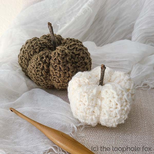 Easy Pumpkin Crochet Pattern shown worked with two pumpkins. A smaller, white pumpkin is closer in the image and a deep, forest green pumpkin sits behind it.