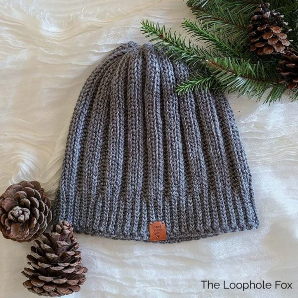 This image shows the ribbed crochet beanie pattern in medium (4) weight, Lion Brand Homeland in Petrified Forest. This is a greyish green color. The beanie is sleek with many more ribs than it's super bulky version.